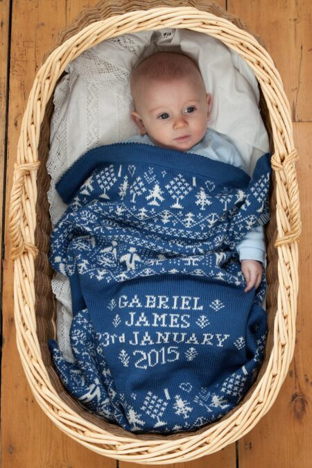 People & Trees personalised baby blanket in HOLKHAM colourway with baby in moses basket